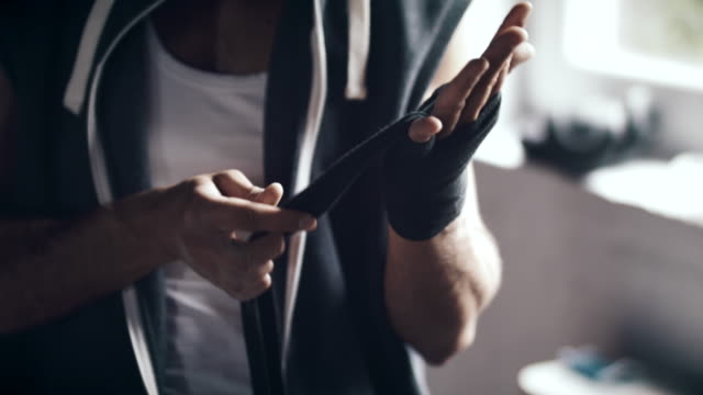Man wrapping hands before workout video
