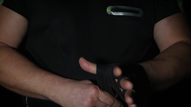 man wraps his hands in black textile bandage for sports man wraps his hands in black textile bandage for sports, close up, slow motion human joint stock videos & royalty-free footage