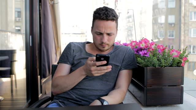 man writes sms in cafe - solo un uomo giovane video stock e b–roll