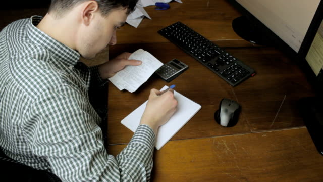 Man writes with payment checks to notebook video
