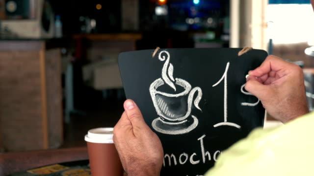 Man writing coffee price on chalk board