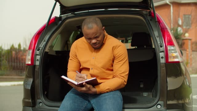 Man writing down daily schedule seated in car trunk