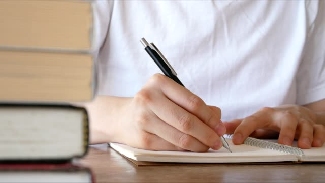 man writing on notebook at desk with stack of books in foreground - writing and literature concept