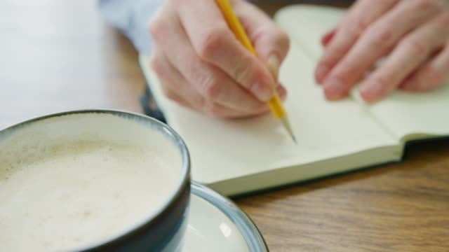 Man Writing Recipe In Book By Coffee Cup At Table
