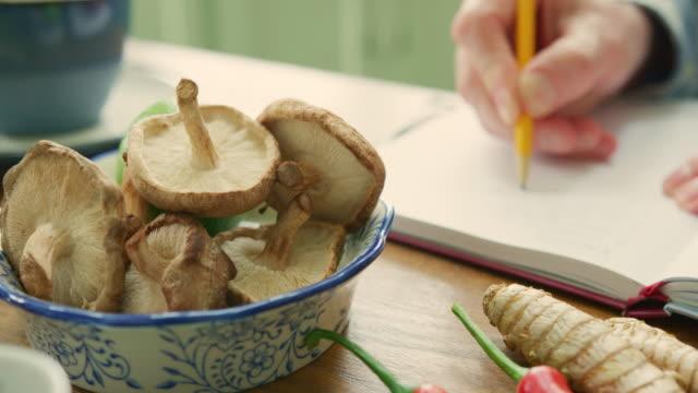 vidéos et rushes de homme qui rédige la recette dans le livre de champignons dans un bol - recette