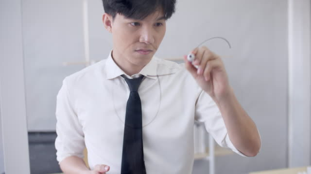 Man Writing Word on Glass Board