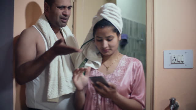 man yelling on her wife using bathroom for longer time. - bagno domestico video stock e b–roll