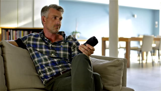 Man zapping TV and bored A middle aged man is watching TV, zapping constantly and leaving at the end. changing channels stock videos & royalty-free footage