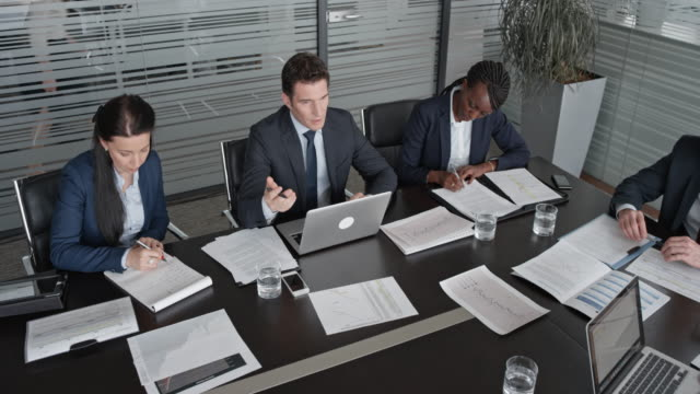 Management accountant talking in a meeting with his colleagues and the chief financial officer