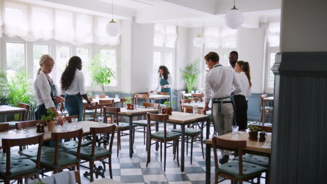 Management And Staff Preparing Tables Before Restaurant Opens Restaurant staff laying tables for service in empty restaurant with management looking on - shot in slow motion wait staff stock videos & royalty-free footage