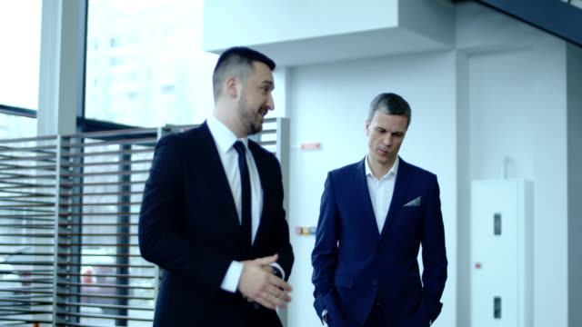 Manager and client walking to car Slow motion of adult agent in suit talking to customer and walking to new car in showroom. salesman stock videos & royalty-free footage