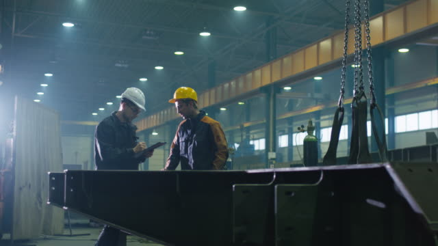manager and engineer worker in hardhats are having a conversation in a heavy industry factory. - metallurgia video stock e b–roll