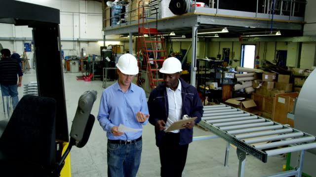 manager e forchetta sollevare operatore discutere le consegne - metal robot in logistic factory video stock e b–roll