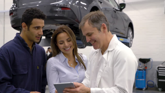 Manager and mechanic showing a customer the list of auto parts they fixed on tablet video