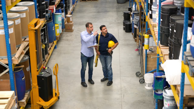 manager and worker walking between the stock of a warehouse giving instruction to worker - imbracatura video stock e b–roll