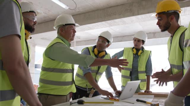 chef på en byggarbetsplats handskakning med ung man ansluter sig till hans team - kroppsarbetare bildbanksvideor och videomaterial från bakom kulisserna