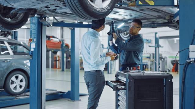 manager kontrollerar data på en tablet pc och förklarar uppdelningen till en mekaniker. bilservicepersonal inspekterar bilens botten med en led-lampa. modern ren verkstad. - garage bildbanksvideor och videomaterial från bakom kulisserna