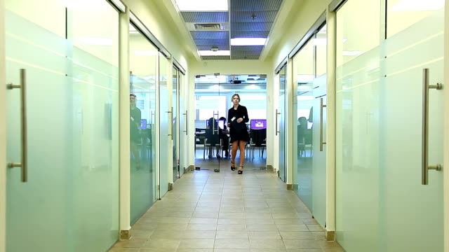 Manager comes out of conference hall and walks along corridor video