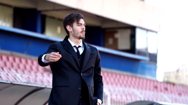 Manager doing his job Young charming soccer manager training his team on a soccer stadium, standing and observing the game. coach stock videos & royalty-free footage