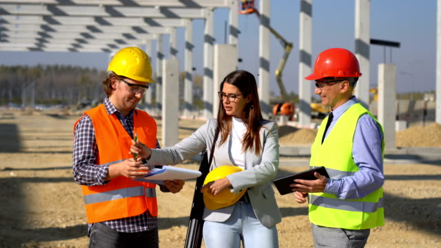 Manager, Female Architect and Foreman Meeting on Site Under Construction