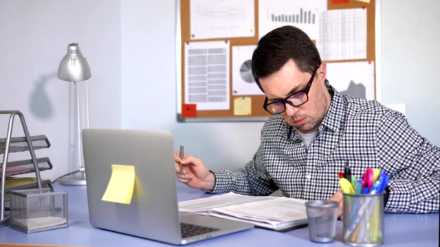 vidéos et rushes de gestionnaire remplit les formulaires papier en milieu de travail et se penche sur le moniteur de l'ordinateur portable - pratique médicale
