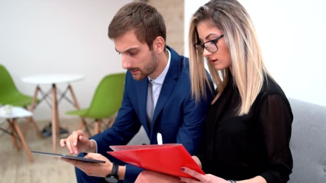 Manager flirting with his secretary A manager and his secretary are sitting on a sofa in an office. He is browsing his tablet, she is writing something. Then he starts staring at her longingly as she begins to smile. employee engagement stock videos & royalty-free footage