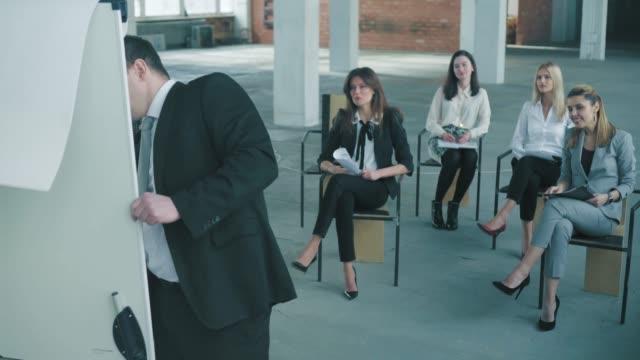 ビジネススーツを着たマネージャーが聴衆にプレゼンテーションを行います。クリエイティブなオフィスインテリア。コワーキングライフ。オフィスワーカー ビデオ