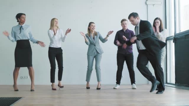 ビジネススーツを着たマネージャーが感情的に踊っている。ビジネスチームは手をたたき、踊り、成功を祝います。素晴らしい気分。オフィスライフ。労働者は祝う。コワーキング ビデオ
