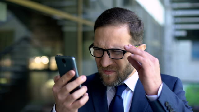 Manager in eyeglasses trying read smartphone message, poor eyesight, health care Manager in eyeglasses trying read smartphone message, poor eyesight, health care eyesight stock videos & royalty-free footage