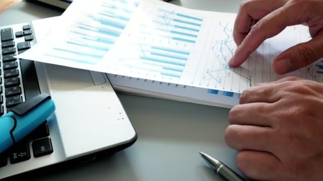 vidéos et rushes de gestionnaire en bureau analysant le rapport d'affaires avec des diagrammes financiers. - book