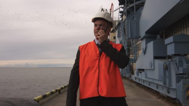 manager cargo harbor sitesinde iki yönlü radyo kullanıyor. - ultra yüksek çözünürlüklü televizon stok videoları ve detay görüntü çekimi