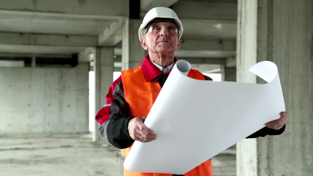 Manager of the works at construction site Worker in white hard hat with building drawings at project site. Manager of the works at construction site craftsman architecture stock videos & royalty-free footage