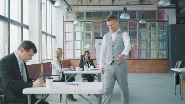 Manager streichelt im Büro, geht zu einem Kollegen, setzt sich an seinen Schreibtisch, schaut sich seine Dokumente an, wirft sie dann weg. Ein Kollege ist empört. Modernes trendiges Büro-Interieur. Büroleben – Video