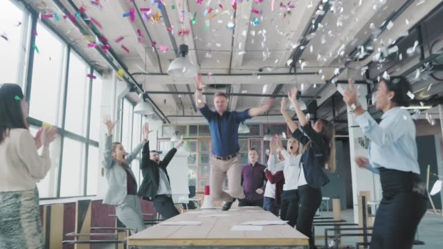 vídeos de stock e filmes b-roll de manager start to dance on the table, sings into a megaphone, accelerates and slide on lap. colleagues blow up flappers with confetti. employees celebrate success. corporate party business team - megafone