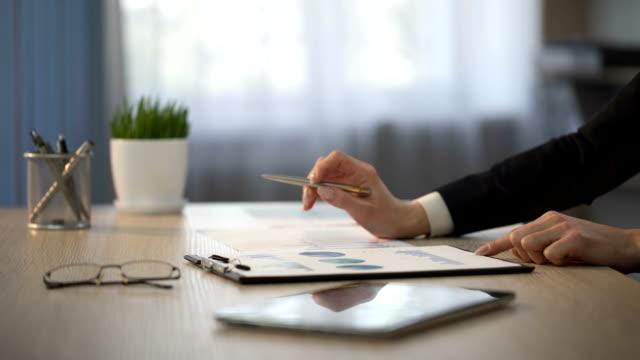 chefen att ta titt på statistiska diagram, lån granskning kontrollera, finansiell balans - accounting bildbanksvideor och videomaterial från bakom kulisserna
