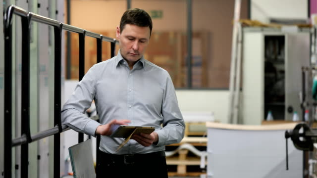 Manager using digital tablet at printing plant video