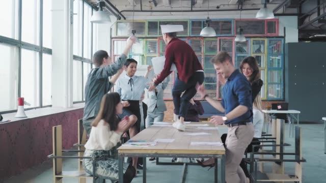 マネージャーは、近代的なトレンディなオフィスでテーブルの上で楽しく踊り、成功を祝います。コーポレートパーティービジネスチーム。コワーキング。同僚のエンターテイメント ビデオ