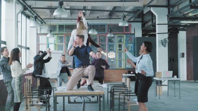 Manager freuen sich über Erfolg und streuen Geld und Dokumente. Kollegen feiern das Ende des Projekts, haben Spaß am Tanzen auf dem Tisch. Corporate Party Business Team. Modernes trendiges Bürointerieur – Video