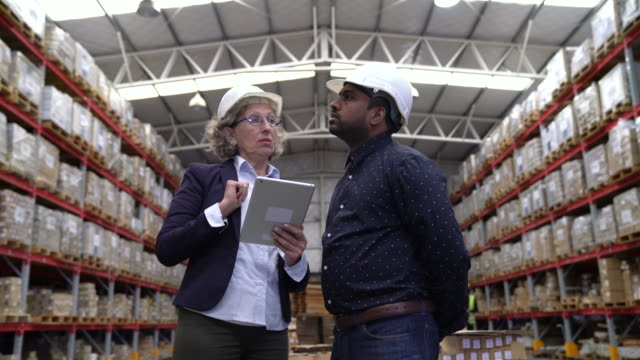 Managers with tablet pc discussing in warehouse Dolly shot of supervisors looking at merchandise and using digital tablet. They are discussing while standing in warehouse. Confident managers are making checklist together. quality control stock videos & royalty-free footage