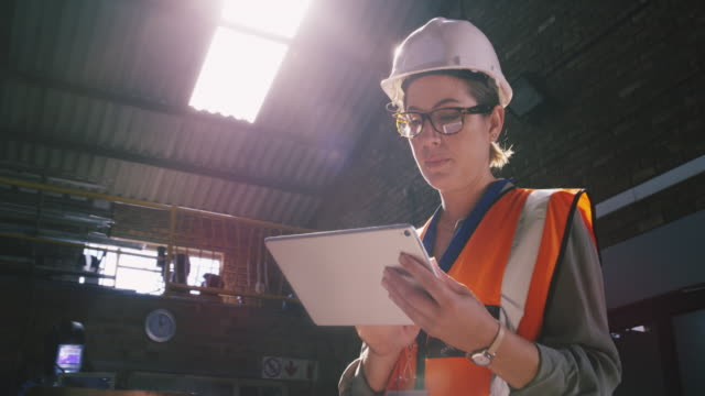 Managing site demands with digital tech 4k video footage of a young engineer using a digital tablet in an industrial place of work work helmet stock videos & royalty-free footage