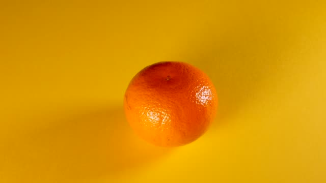 mandarin tangerine being peeled by itself and served on a yellow background stop motion animation - funky video stock e b–roll
