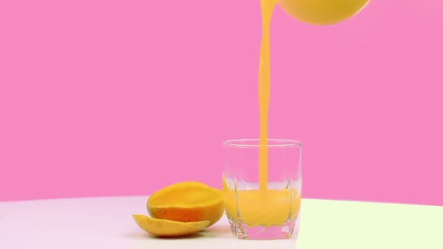 mango juice isolated on a pink background - healthy green juice video stock e b–roll