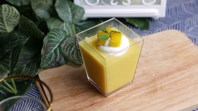 vidéos et rushes de panna cotta de mangue un dessert riche et soyeux servi dans une coupe claire. - vanille
