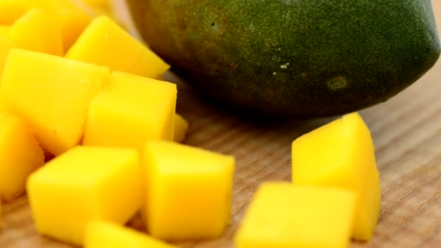 Mango pieces on a wooden board. video