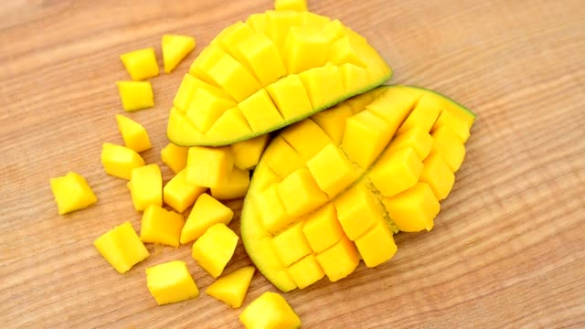 Mango pieces on a wooden board. Shooting in the movement. mango stock videos & royalty-free footage