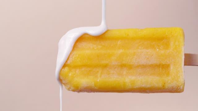 vídeos y material grabado en eventos de stock de popsicle de mango con cobertura de chocolate blanco - glaseado para postres