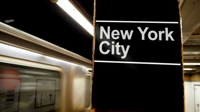 Manhattan Subway Leaves the Platform with New York City Sign A Manhattan subway leaves the station near a hypothetical New York City identification sign on a pillar. subway platform stock videos & royalty-free footage