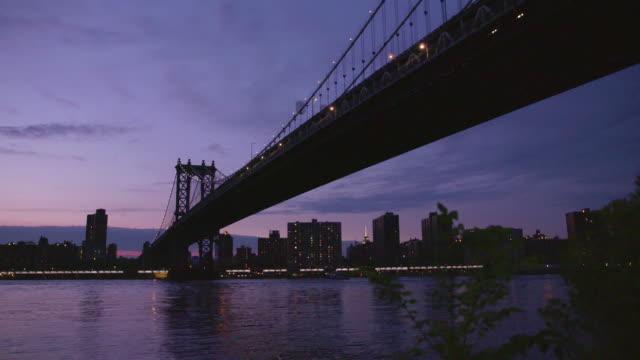 Manhatten bridge with the distinctive New York skyline in background at sunset video