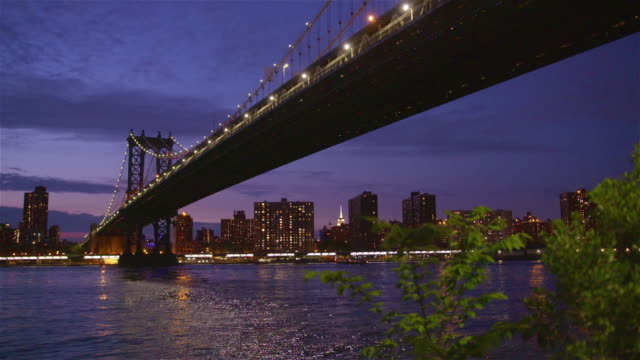 Manhatten bridge with the distinctive New York skyline in background at sunset video