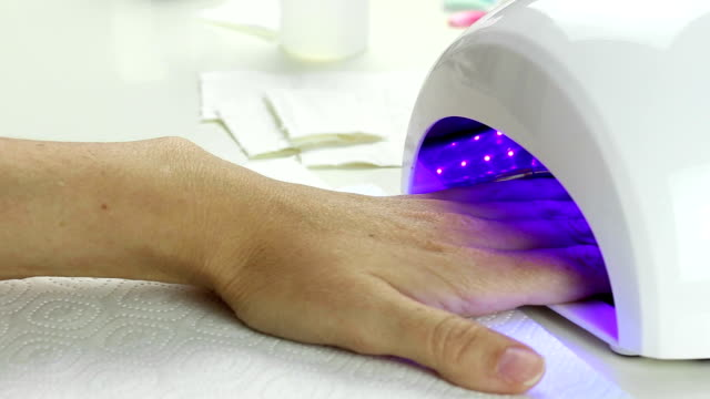 Manicure in process - putting hand and curing gel varnish in nail LED lamp video